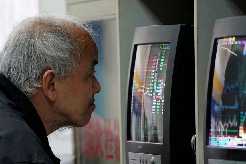 An investor looks at a screen showing stock information at a brokerage house in Shanghai.