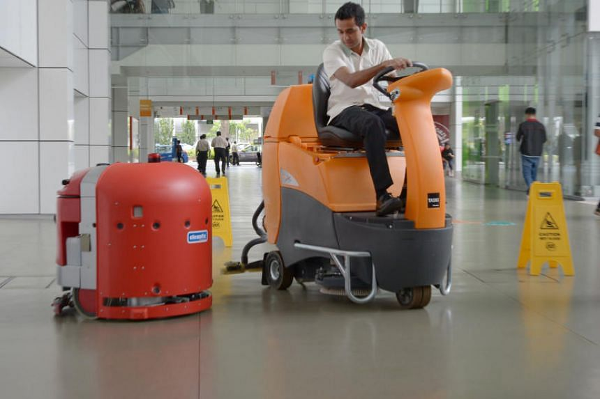 A cleaning robot (left) and a human-operated cleaning machine at NUH, June 27, 2016.