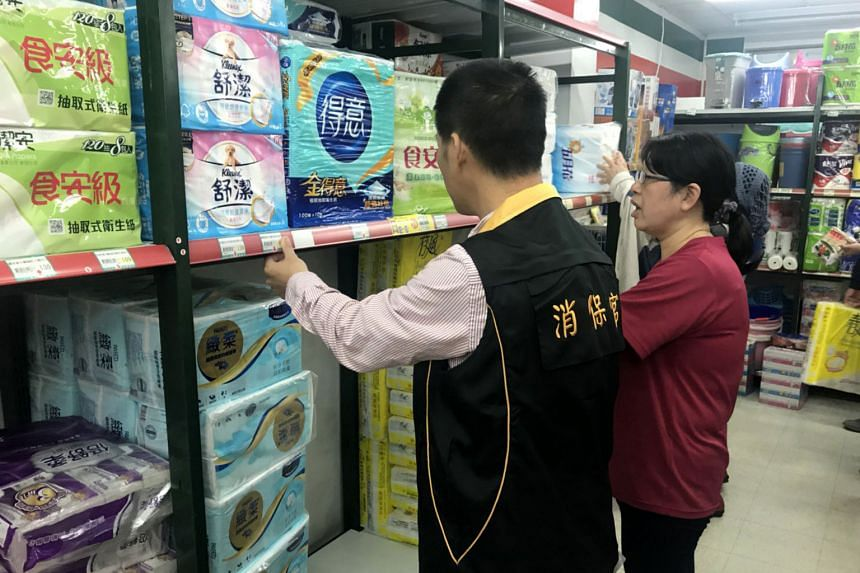 A photo made available by the Kaohsiung City government shows an inspector (left) checking toilet paper prices at a store. Panic buying started after major supermarkets were informed by toilet paper manufacturers of a 10 per cent to 30 per cent price