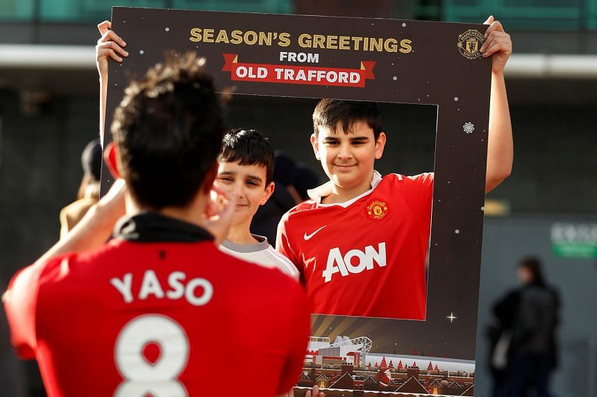 Manchester United fans in good cheer outside Old Trafford before the game against Burnley on Boxing Day last year. Having a winter break in February will be a compromise between clubs' demands for a rest in mid-season and fans who insist on having th