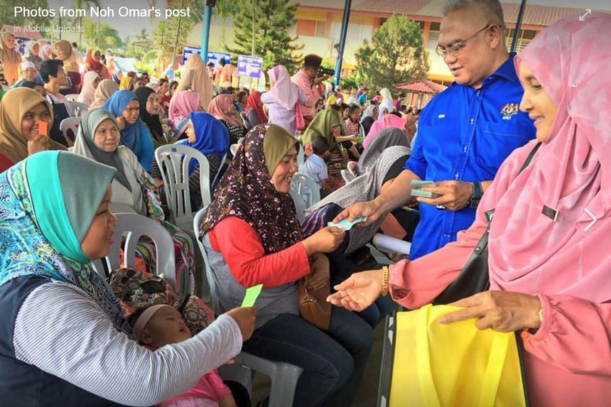 Urban Wellbeing, Housing and Local Government Minister Noh Omar handing out cash to parents in a Selangor ward on Feb 2. The photo has caused an online furore.