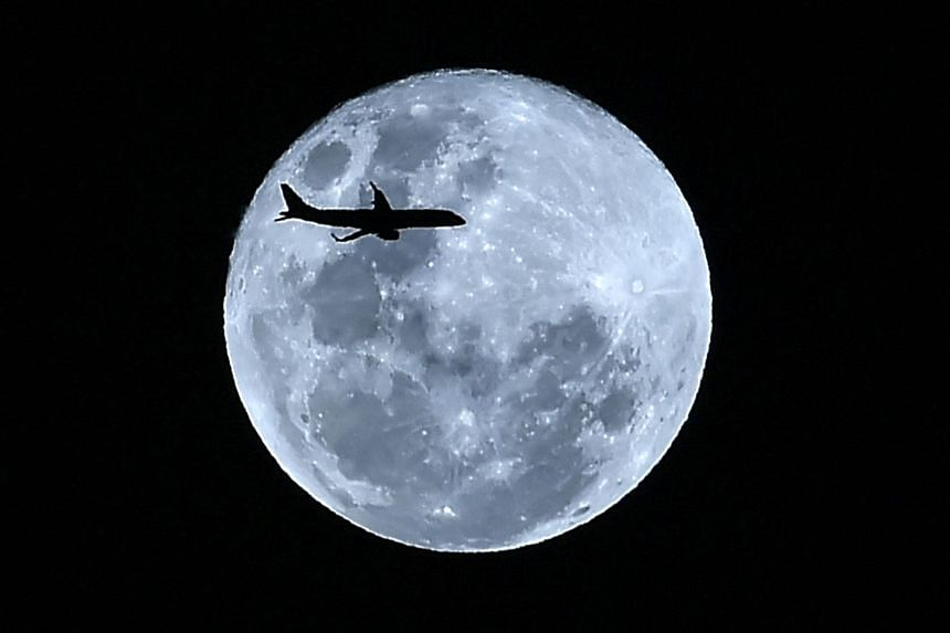 "A plane silhouetted against the ""super blue moon"" over Cali, Colombia on Jan 31, 2018."