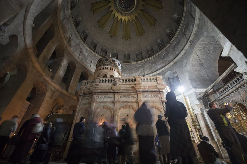 Christian devotees pray at the Church of the Holy Sepulchre in Jerusalem's old city as it reopens on Feb 28, 2018, after three days of closure by the heads of the Christian Churches leaders in protest against Israeli tax measures.