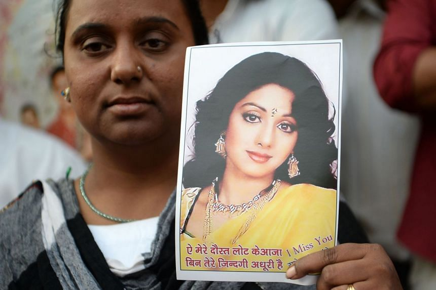 A woman holds a picture of late Bollywood actress Sridevi Kapoor as she stands outside her house before Sridevi's funeral in Mumbai on Feb 28, 2018.