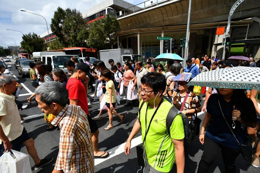 A crowd crossing a traffic junction along Ang Mo Kio Avenue 3 near an MRT station.