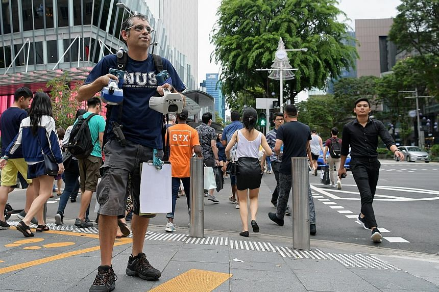 Dr Erik Velasco with air quality measurement devices at Orchard Road. His study found that commuters travelling via bus or taxi breathed in up to two times more harmful particles compared with taking the MRT.