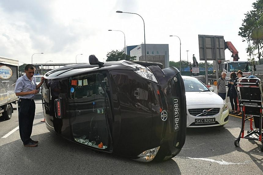 A taxi driver standing by his vehicle after an accident in Braddell Road in January last year. Taxis, which make up a mere 2.4 per cent of the total vehicle population here, accounted for 13 per cent of accidents reported last year, statistics gather