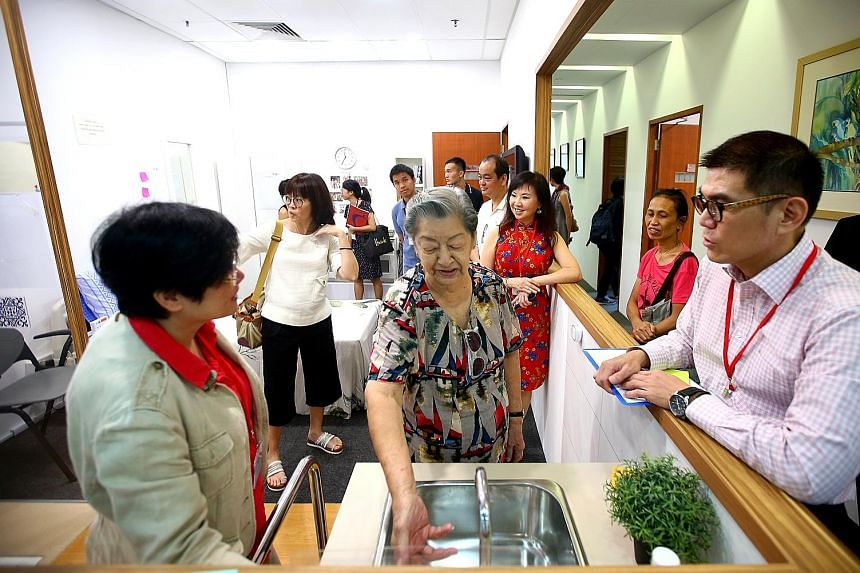 Madam Koh Seow Kim, 86 (centre), getting a hands-on tour of a mock-up studio flat at the Centre For Seniors open house in Bishan yesterday. The centre will be holding roadshows every two months to inform seniors about the new website, and teach less