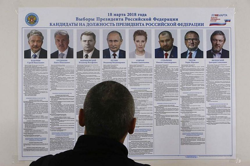 A voter looks through a broadsheet with information about the candidates during the early voting ahead of the Mar 18 presidential election in a settlement on the Pechora Sea island of Kolguyev in Russia on Feb 28, 2018.
