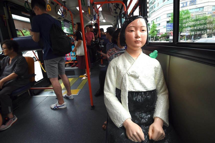 A statue of a teenage girl symbolising former 'comfort women' who served as sex slaves for Japanese soldiers during World War II, is mounted in a bus running through downtown Seoul on Aug 14, 2017.