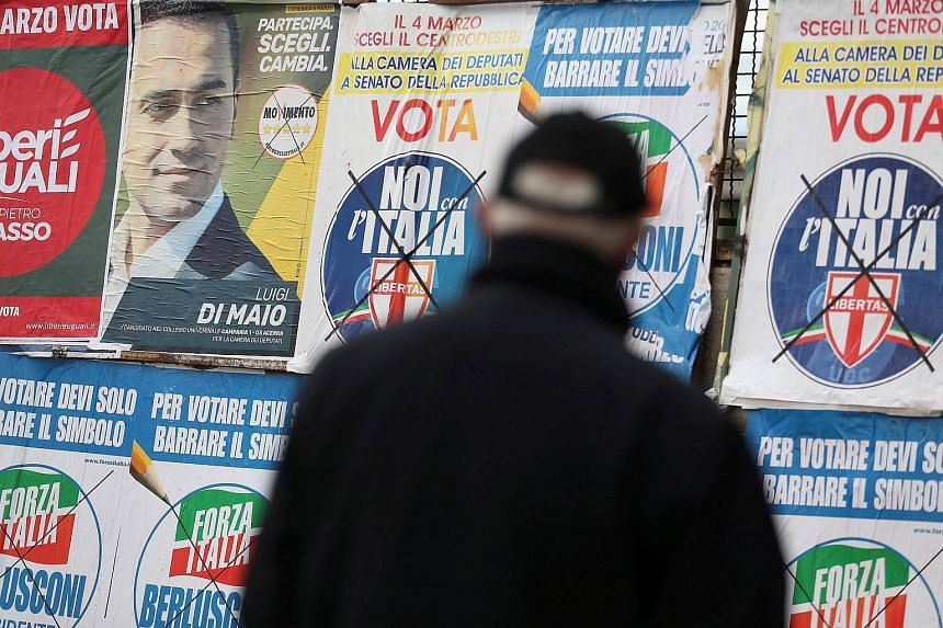 A man stands to look electoral posters in Pomigliano D'Arco, near Naples, Italy, on Feb 21, 2018.