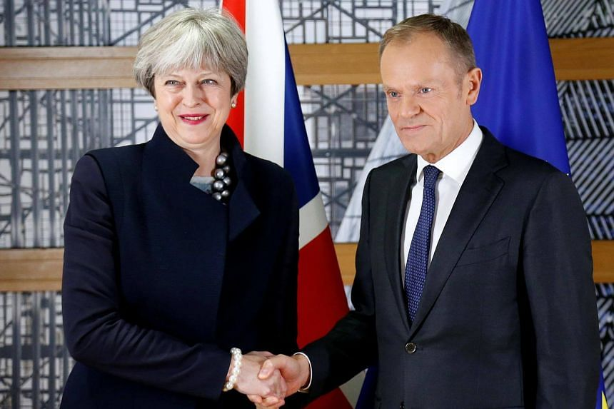 British Prime Minister Theresa May and European Council President Donald Tusk shake hands as they pose ahead of a meeting in Brussels, on Dec 4, 2017.