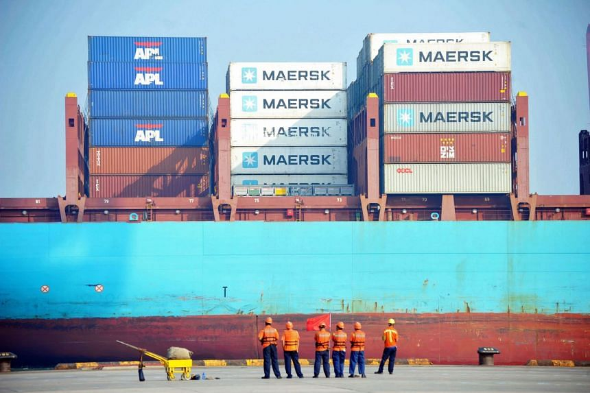 Chinese workers look at a cargo ship loaded at a port in Qingdao, Shandong province.