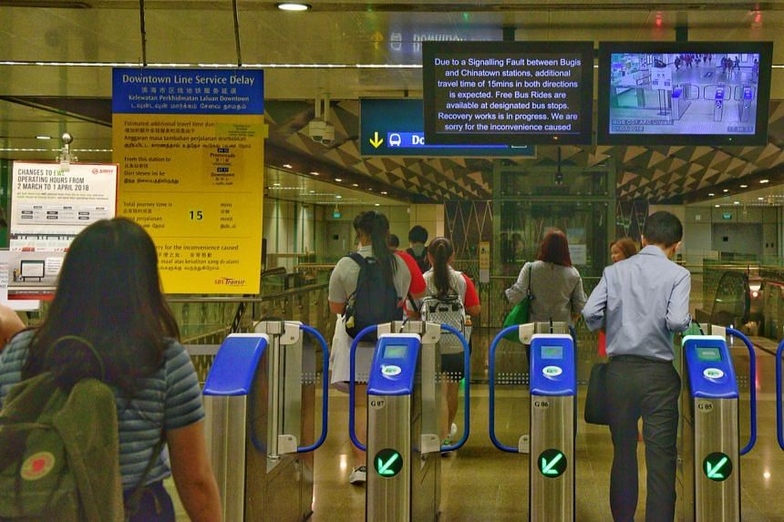 A sign announcing that the Downtown line service will be delayed by 15 minutes at Bugis MRT station.