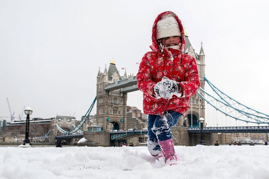 A girl playing close to London's Tower Bridge yesterday as Britain is hit by sub-zero temperatures. More heavy snow is expected in the coming days.