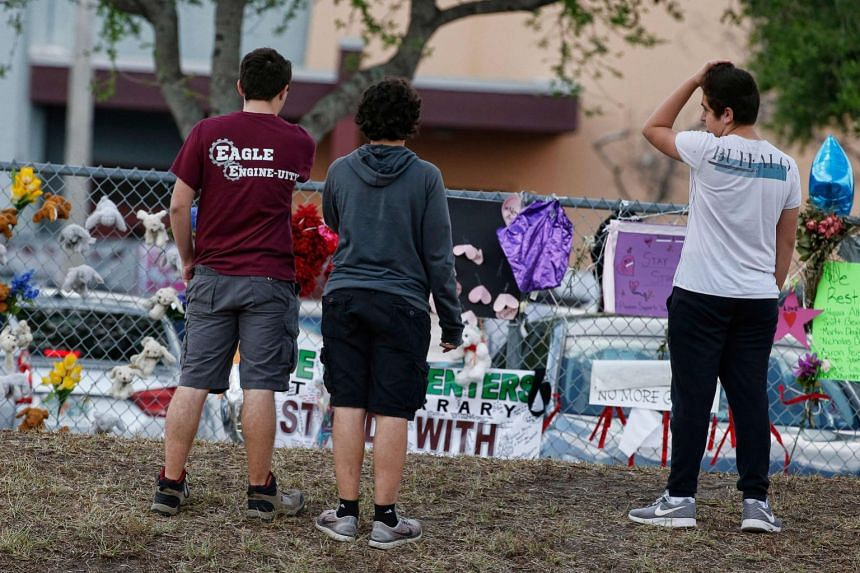 Marjory Stoneman Douglas High School students stop to look at a memorial following their return to school in Parkland, Florida.