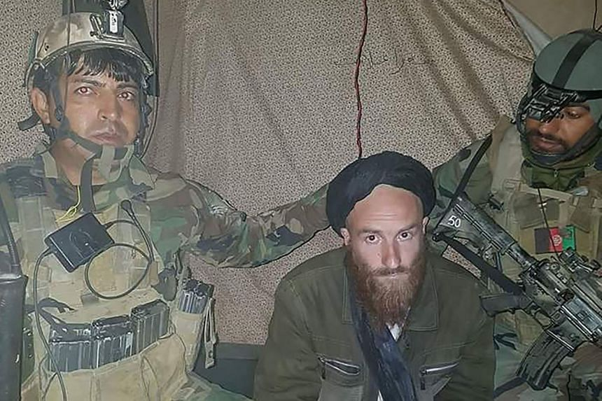 A man (centre) who identified himself as a German national was arrested by Afghan commandos in Helmand province on Feb 28, 2018.