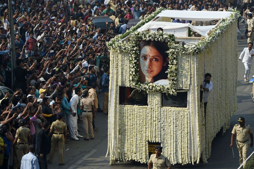 Indian fans watch as the funeral cortege of the late Bollywood actress Sridevi Kapoor passes through Mumbai, ahead of her cremation on Feb 28, 2018.