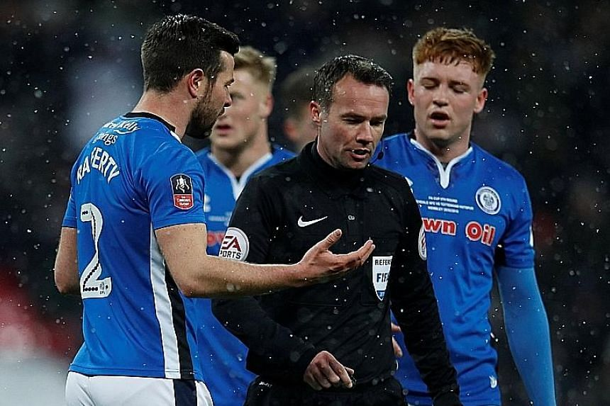 Left: Tottenham striker Fernando Llorente heading home to seal his hat-trick against Rochdale in their FA Cup fifth-round replay. Below: Rochdale's Joe Rafferty speaking with referee Paul Tierney after the match official decided to give a penalty to