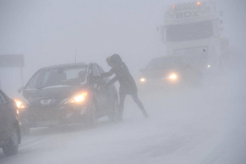A woman seeks shelter from the blizzard in her stranded car near Sjobo, Sweden, on Feb 27, 2018.