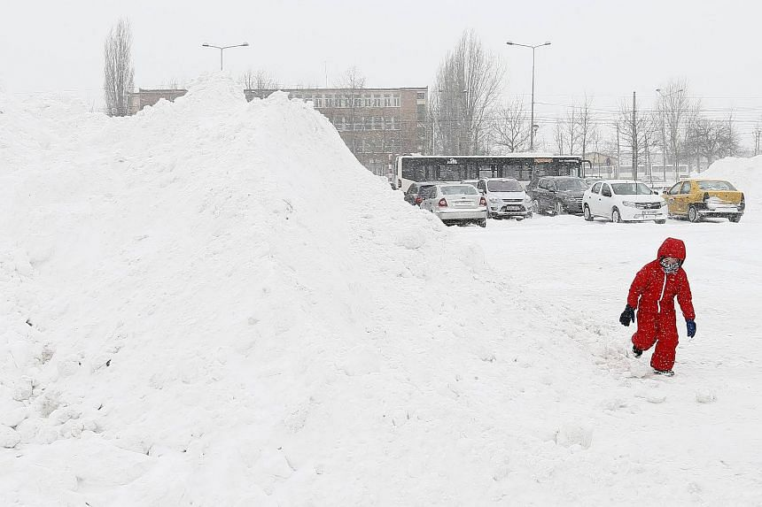 A Romanian child plays with a big pile of snow at a shopping mall parking lot in Bucharest, Romania, on Feb 27, 2018.