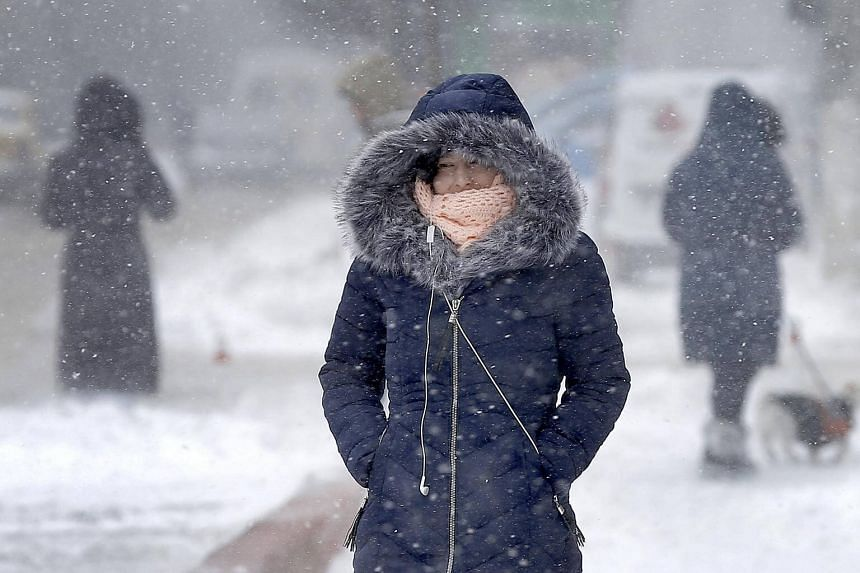 A Romanian young woman walks against the blizzard in Bucharest, on Feb 27, 2018.