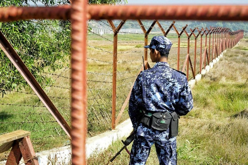 A Myanmar border guard stands next to fencing in a field on the outskirts of Maungdaw in Rakhine state on Jan 24, 2018.