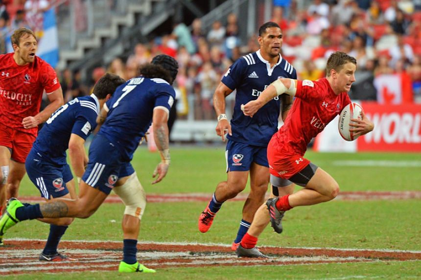 Cananda's Lucas Hammond (right) evades the American defence to score the winning try in the Cup Final of the HSBC Singapore  Sevens at the National Stadium on April 16, 2017.