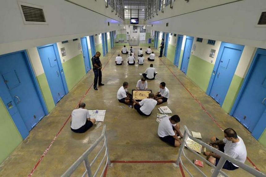 A Prison Officer looking on as inmates engage in interactive indoor recreational activities at the Changi Prison Complex.