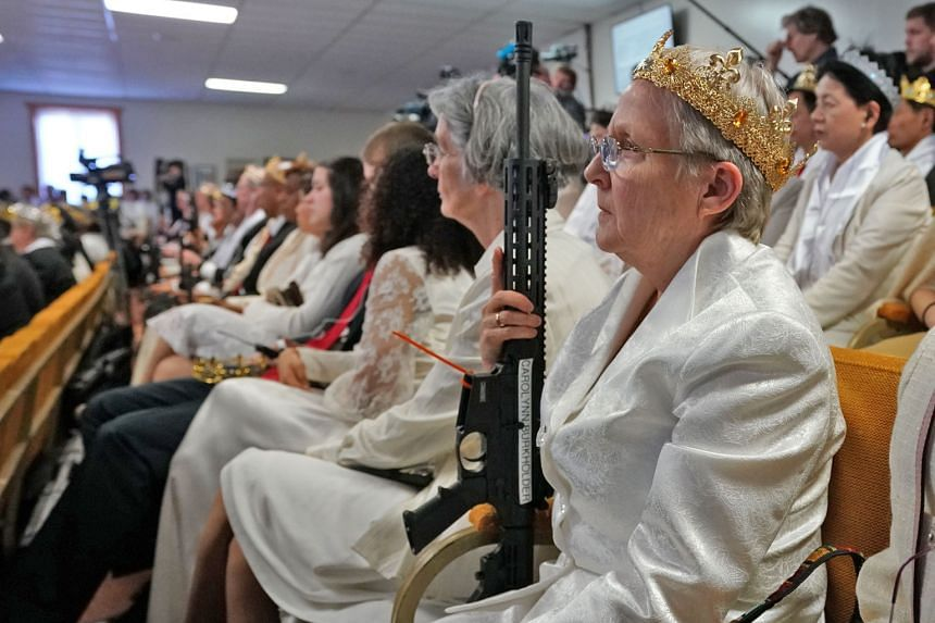 Worshippers at the World Peace and Unification Sanctuary in Newfoundland, Pennsylvania, holding weapons during a service on Wednesday. Hundreds of worshippers gathered inside the church at a blessing ceremony for couples featuring their AR-15 rifles.