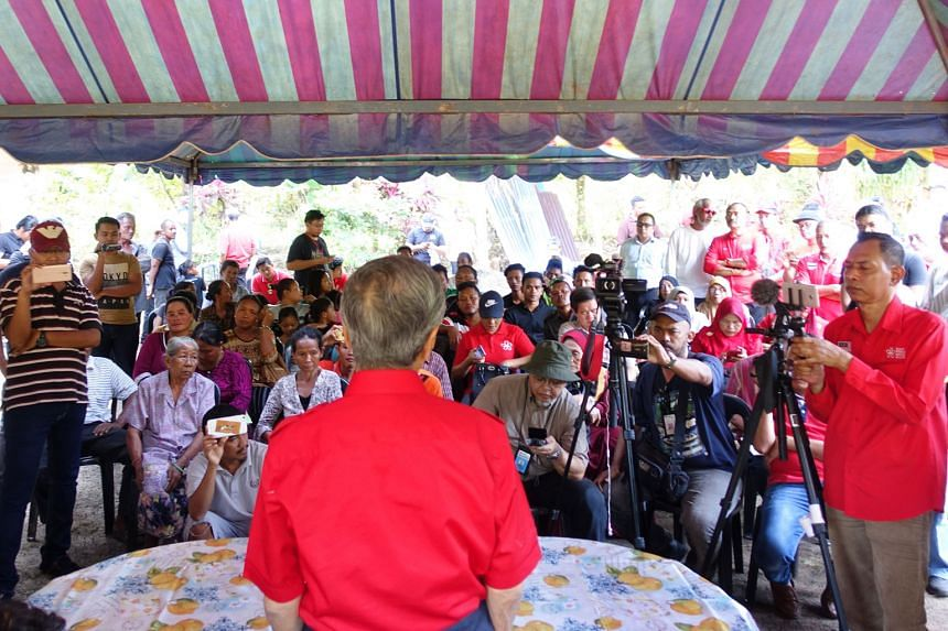 Opposition leader Mahathir Mohamad speaking to indigenous people during a visit on Wednesday to Kampung Gumum, near the Felda Chini 2 settlement in the Malaysian state of Pahang.