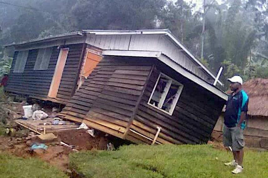 A local stands next to a damaged house near a landslide in the town of Tari after an earthquake struck Papua New Guinea's Southern Highlands on Feb 27, 2018.