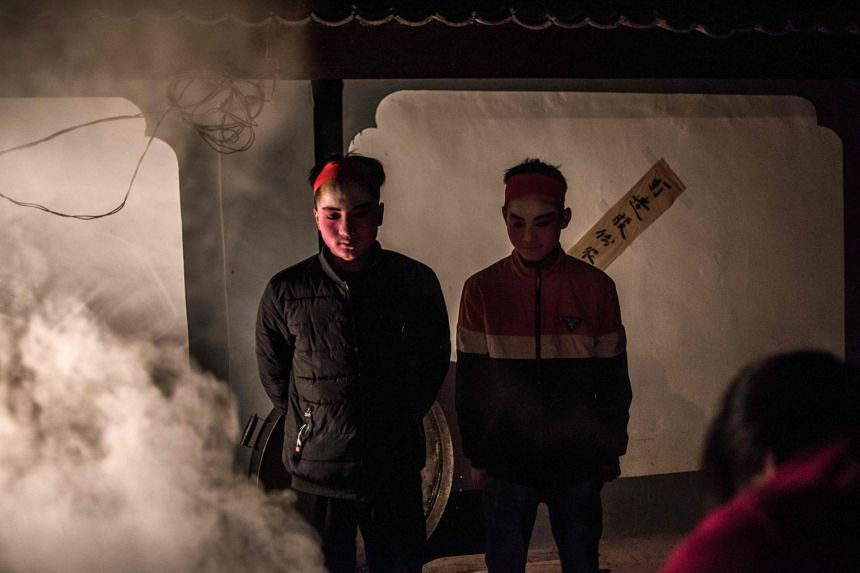 Villagers stand beside a cooking fire to get warm prior to a parade at the She Huo festival on the outskirts of Longxian, China, on Feb 28, 2018.