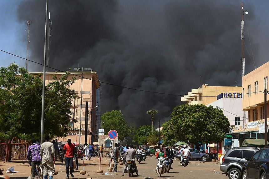 Black smoke rising as the capital of Burkina Faso came under attack yesterday. Witnesses said armed men got out of a car and opened fire on passers-by before heading towards the French embassy, in the centre of the city. A blast later rocked the comp