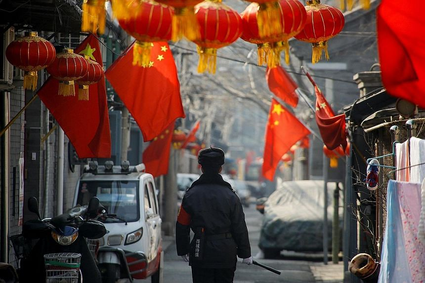A security guard patrolling a residential alley near Beijing's Great Hall of the People, the venue of the plenary session of the National People's Congress, yesterday.