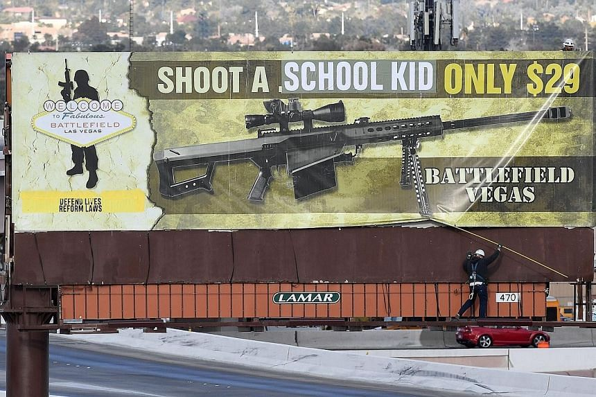 """Workers removing a billboard in Las Vegas on Thursday after vandals struck. The words """"school kid"""" were put over """".50 caliber"""", and """"Defend lives reform laws"""" was added to the ad for a machine gun range."""