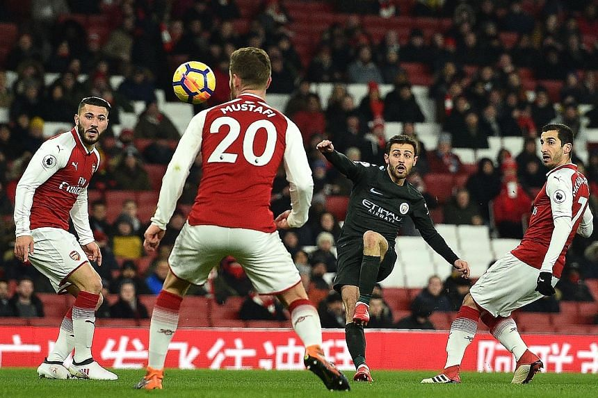 Bernardo Silva bending the ball past Arsenal's defence and beyond the reach of goalkeeper Petr Cech (unseen) to set Manchester City on their way to a 3-0 away rout of the Gunners on Thursday.