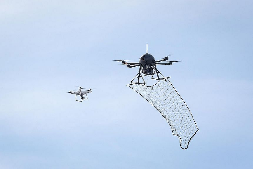 """A """"drone-catcher"""" homes in on an errant drone and catches it with a net. Counter-drone systems are among the features of smart airbases of the future."""