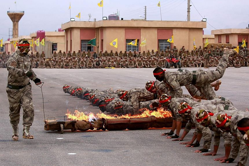 Arab and Kurdish fighters from the Syrian Democratic Forces taking part in a graduation ceremony after completing their military training in Syria's north-eastern Qamishli region on Thursday. They are part of the United States-led military campaign a