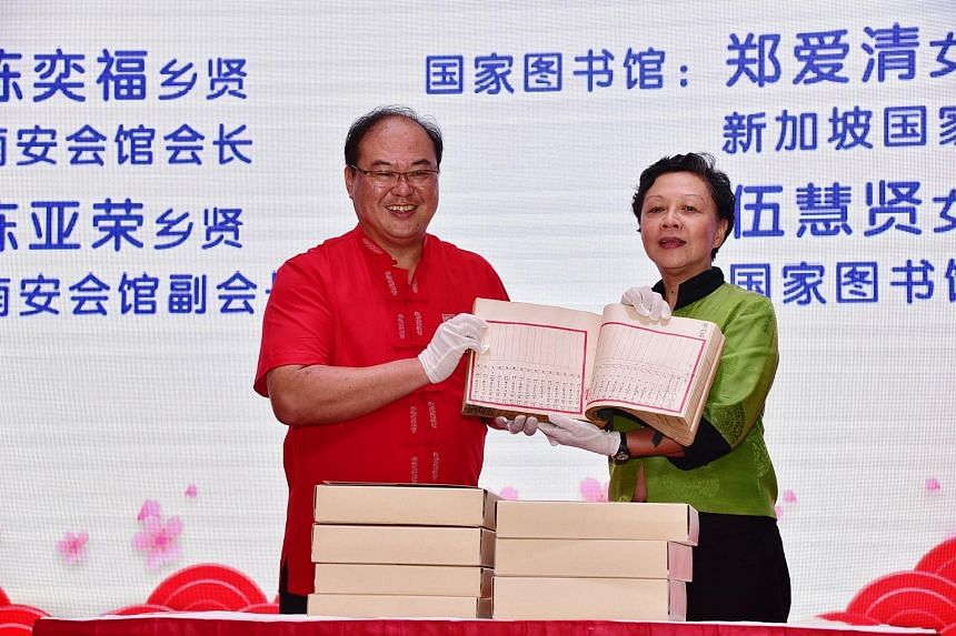 Mr Tan Aik Hock, chairman of the Singapore Lam Ann Association, and National Library Board deputy chief executive Tay Ai Cheng holding one of the seven rare account books on Hong San See temple.