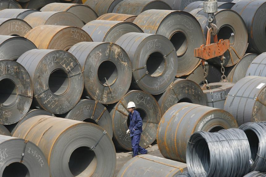 A Chinese worker is dwarfed by huge rolls of steel in a transhipment yard in Shenyang, China, on April 16, 2008.