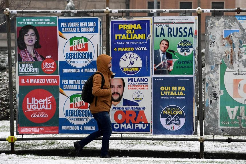 A pedestrian passes in front of election hoardings in Milan on March 1, 2018, prior to the Italian general elections.