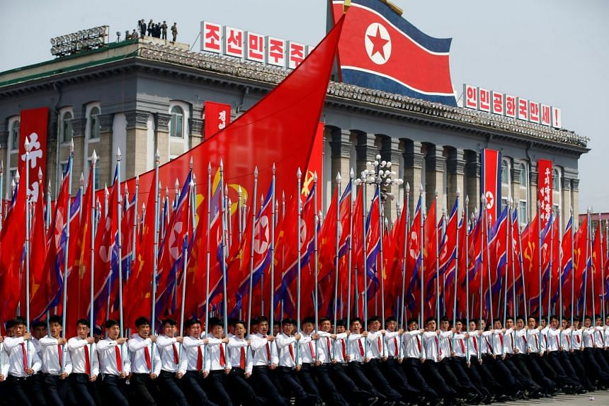 Men carrying flags during a military parade marking the 105th birth anniversary of the country's founding father, Kim Il Sung, in Pyongyang on April 15, 2017.