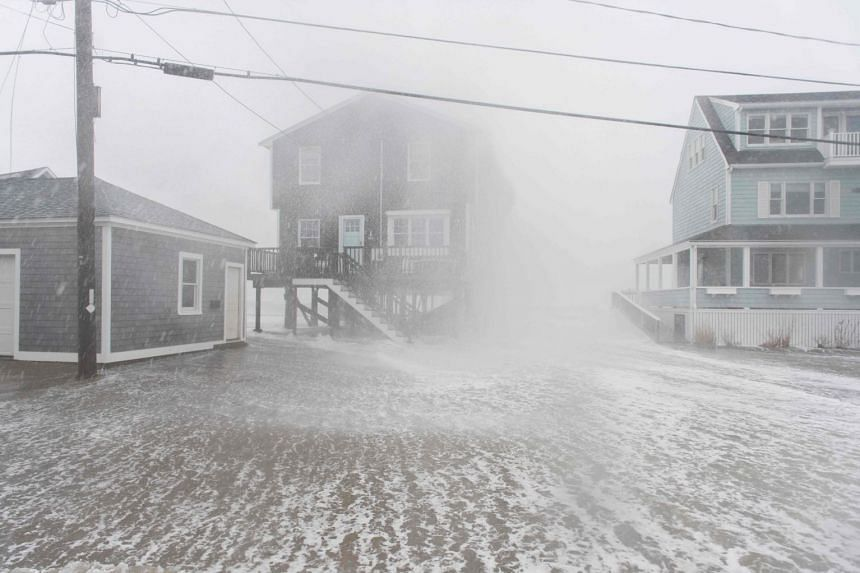 Waves crash into homes in Scituate, Massachusetts on March 2, 2018.