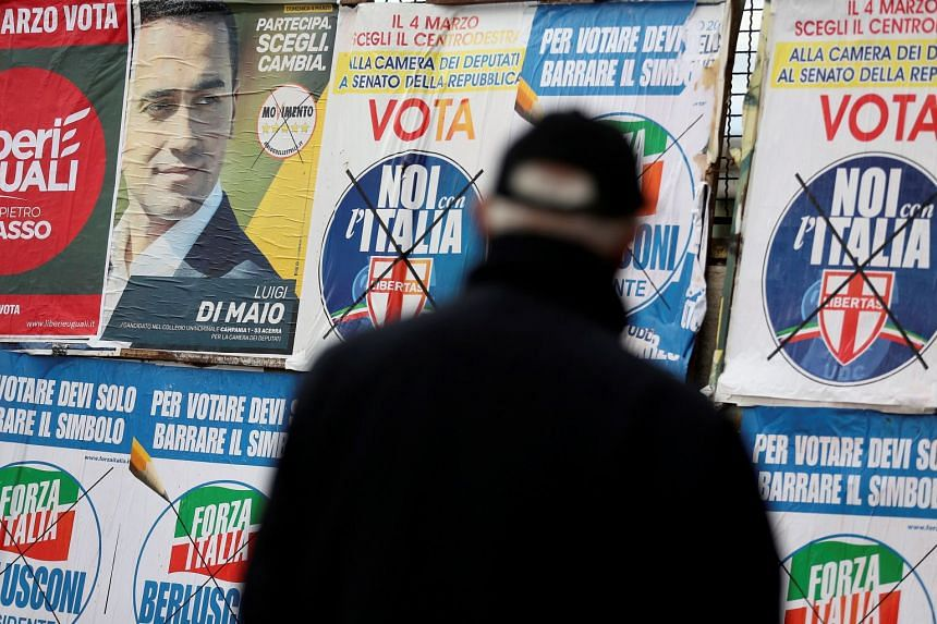A man stands to look at electoral posters in Pomigliano D'Arco, near Naples, Italy, on Feb 21, 2018.