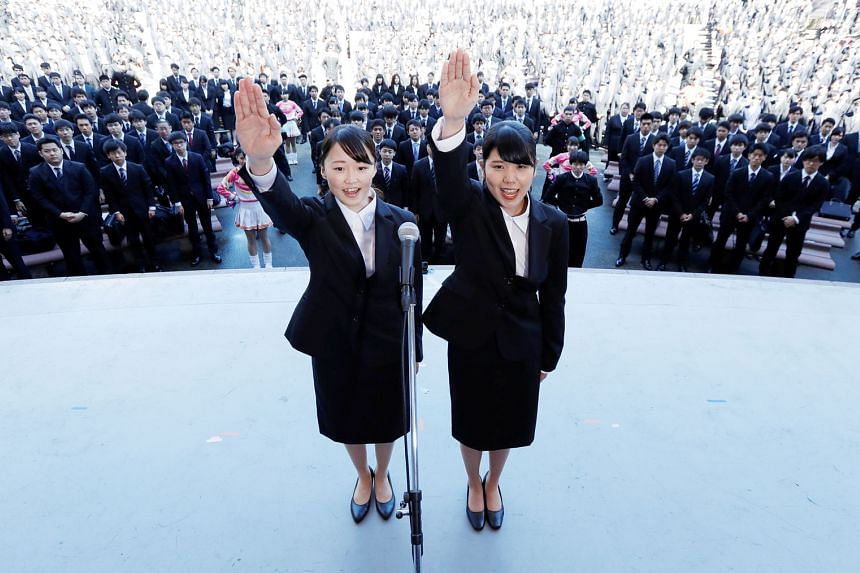 Japanese college students publicly declaring they would do their best to find work during a job-hunting pep rally held to boost their morale, at an outdoor theatre in Tokyo.