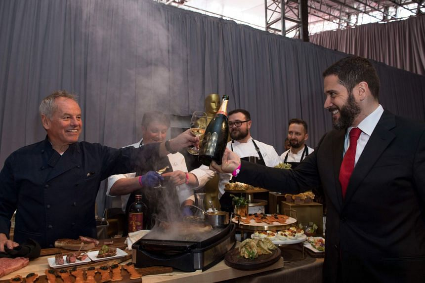 Puck (left) toasts Piper Champagne with Benoit Collard during a preview for the Governors Ball.