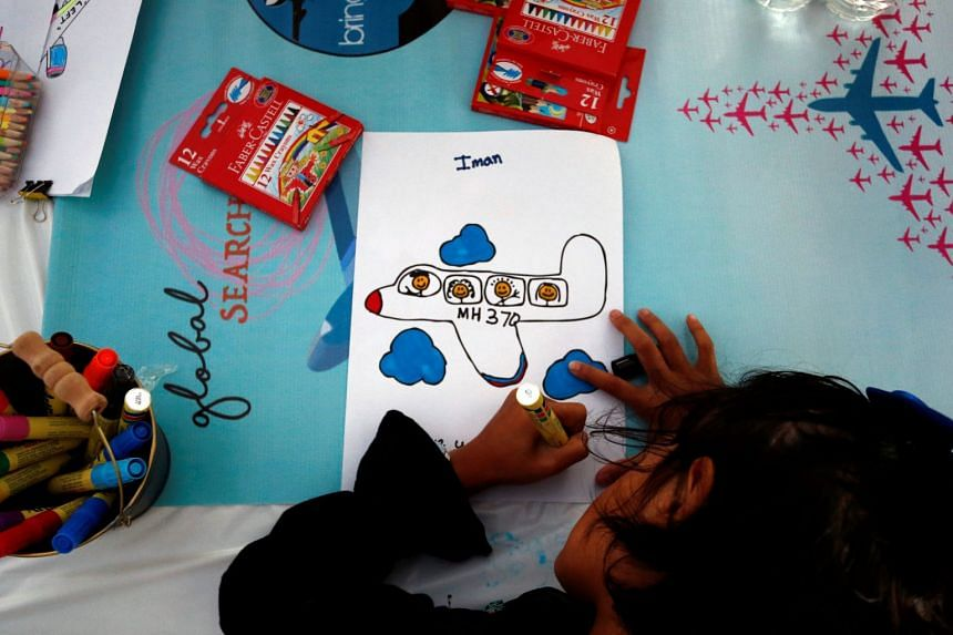 Iman, the daughter of flight attendant Mohamad Hazrin Hasnan, who was onboard the missing Malaysia Airlines flight MH370, colours a plane during its fourth annual remembrance event in Kuala Lumpur on March 3, 2018.