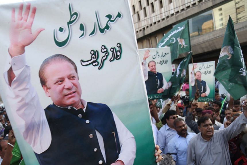 Supporters of former Pakistani Prime Minister Nawaz Sharif hold his portraits during a protest after the Supreme Court barred him from being head of his political ruling party.