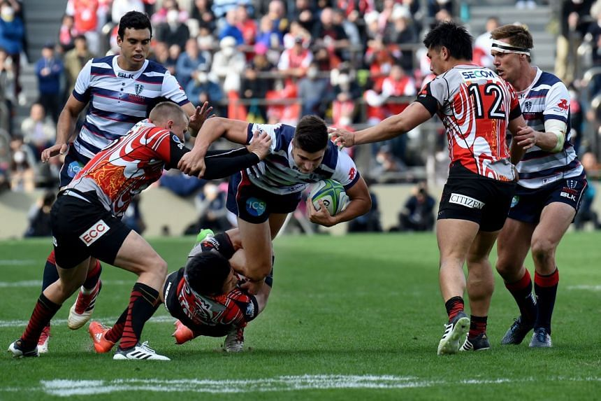 Jack Maddocks of Rebels is tackled by Ryuji Noguchi and Robbie Robinson of Sunwolves during their Super Rugby match at Chichibunbomiya Rugby Stadium in Tokyo on March 3, 2018.